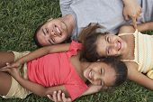 Hispanic father and daughters laying in grass