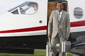 Mixed Race businessman exiting airplane