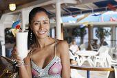 Hispanic woman holding cocktail