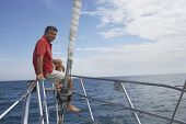 Man sitting on bow of sailboat