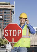 Hispanic construction worker holding stop sign