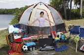 Hispanic girl surrounded by camping supplies