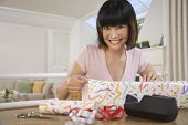 Asian woman wrapping gift