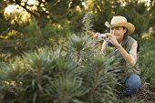 Asian woman taking photograph of plant