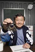 Senior Asian male worker holding keys