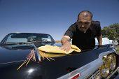 Hispanic man buffing show car