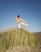 Pacific Islander man jumping on beach