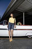 Hispanic woman leaning on convertible
