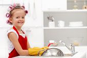 Little housekeeping girl - washing the dishes with a happy smile