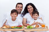 Happy family with two kids having breakfast in bed - healthy eating at home