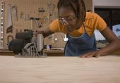 African American woman cutting wood