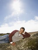 Pacific Islander man laying on rock formation