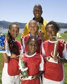 Multi-ethnic children holding soccer trophies