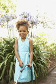Mixed Race girl holding garden hose