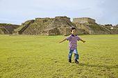 Hispanic boy running in front of ruins, Oaxaca, Mexico