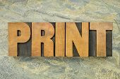 print - a word in vintage letterpress wood type on a green slate rock background