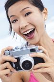Chinese Asian girl young woman laughing taking vacation photograph in a bikini at the beach using a digital camera