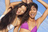 Two beautiful young women or girls, Asian and Latina Hispanic, in bikinis dancing on vacation on a hot sunny beach