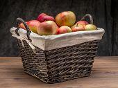 Wicker basket full of delicious apples shot over dark gray background