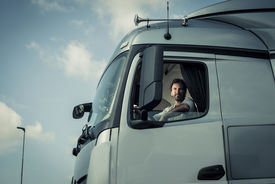 image of truck-stop  - Portrait of a truck driver sitting in cab - JPG