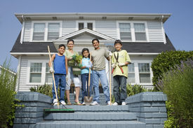 stock photo of pre-adolescents  - Hispanic family with gardening tools in front of house - JPG