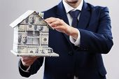 Model of house made of money in male hands on white background