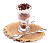 Yogurt, with chocolate cream, chopped chocolate and muesli served in glass jar, on wooden board, isolated on white