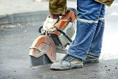 Builder worker with cut-off machine power tool breaking asphalt at road construction site