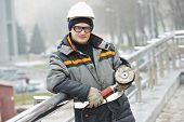 industrial builder worker with ggrinder polishing metal barrier