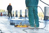 image of flames  - Roofer installing Roofing felt with heating and melting of bitumen roll by torch on flame during roof repair - JPG