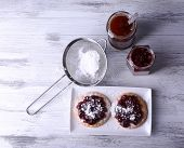 Delicious cookies with jam and powdered sugar on plate on wooden background