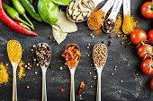 spoons with different spices and vegetables on a black table