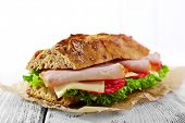 Fresh and tasty sandwich with ham and vegetables on table on light background