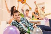 foto of social housing  - Young guy at house party lying on the floor smiling looking at the camera in the background you can see his friends sitting on the couch happy with their hands raised - JPG