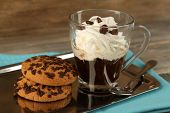 Cup of coffee with cream and cookies on metal tray on wooden background