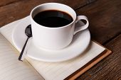 Cup of coffee on saucer with notebook and spoon on wooden table background