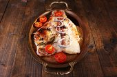 picture of pangasius  - Dish of Pangasius fillet with spices and vegetables in metal tray on wooden table background - JPG