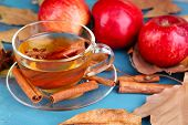 Composition of  apple cider with cinnamon sticks, fresh red apples and autumn leaves on wooden background