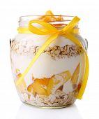 Healthy breakfast - yogurt with  fresh peach and muesli served in glass jar, isolated on white
