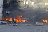 Protestor In Helmet Near Ablaze Car  After Tossing A Stone