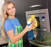 Woman cleaning microwave atkitchen. Female doing housework