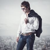 Confident, ambitious good looking man on the top of city with a jacker his shoulder.