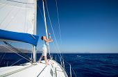 Young man standing on the yacht in the sea at sunny day