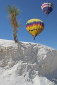 Two balloons over white sands