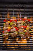 stock photo of kababs  - Beef kabobs on the a flaming hot grill with vegetables - JPG