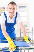 Smiling man cleaner wearing yellow gloves and cleaning office table