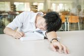 Asian Student Lying And Sleeping On The School Desk