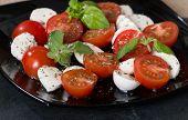 foto of black-cherry  - Italian Caprese salad with cherry tomatoes and baby mozzarella on black plate - JPG