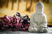 picture of garden sculpture  - closeup of small sculpture of buddha over white pebbles with pink flowers in the background