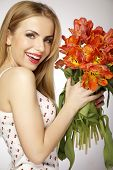 Beautiful sensuality and attractive sexy smiling spring blonde young adult girl with the bouquet of red and yellow tulips flowers isolated on a white background